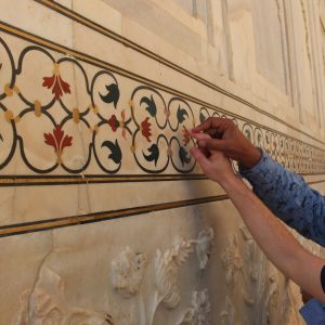 touching the flower mosaics patterns of the Taj Mahals