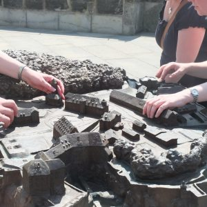 Some hands are exploring the tactile model of Koenigstein Fortress in the Saxonian Swiss
